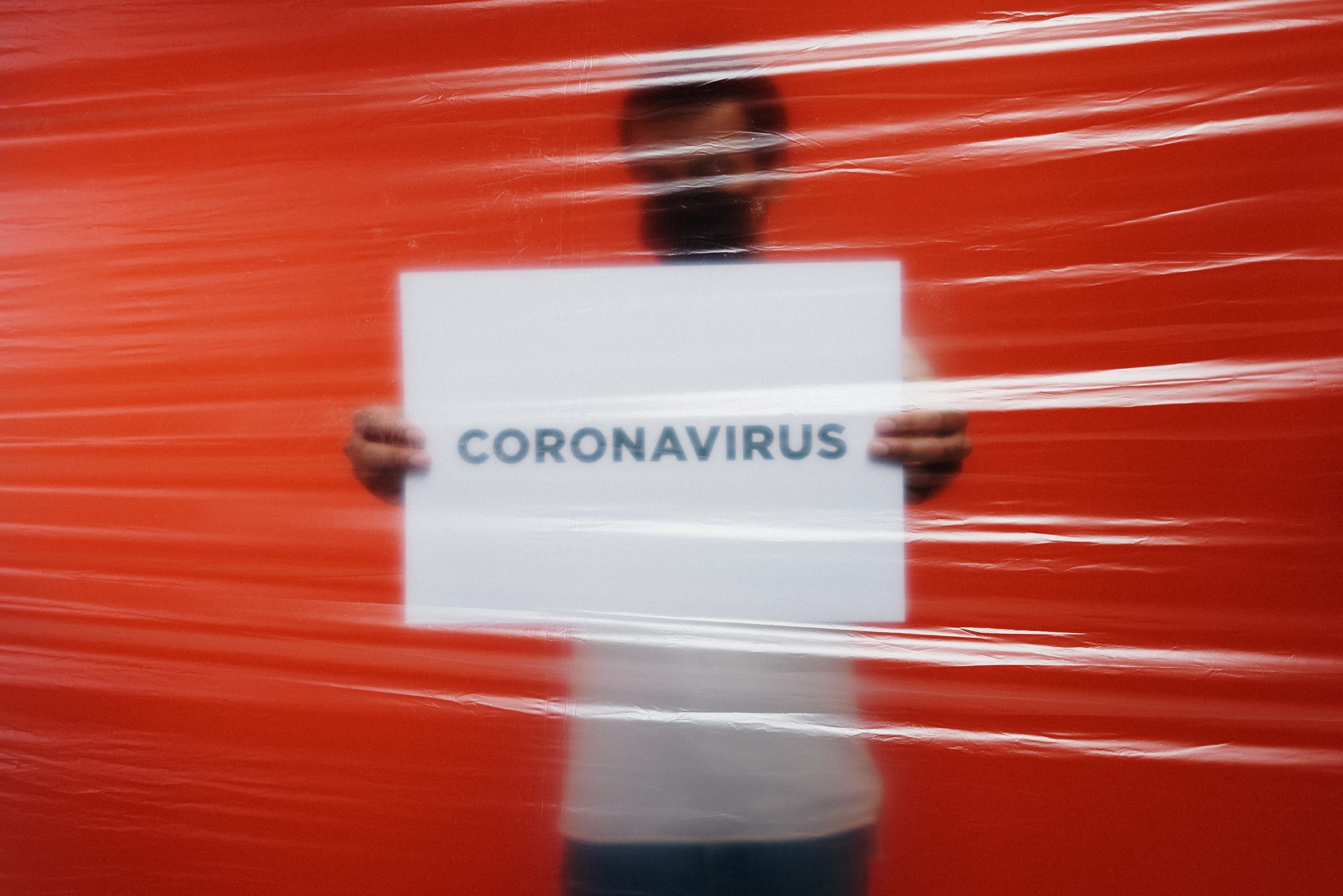 COVID19 man behind a plastic holding a poster of coronavirus 3952185 scaled