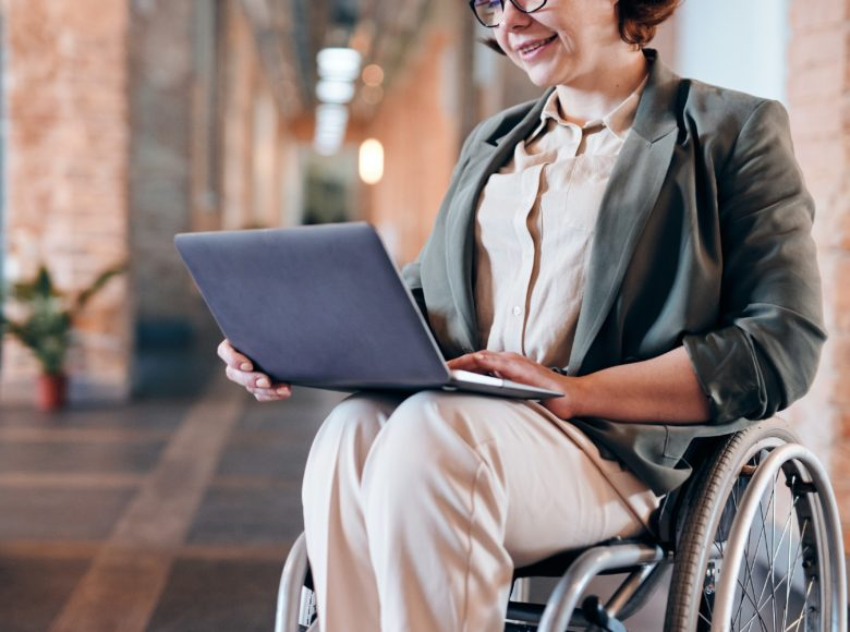 Disability photo of woman sitting on wheelchair while using laptop 4064417 scaled