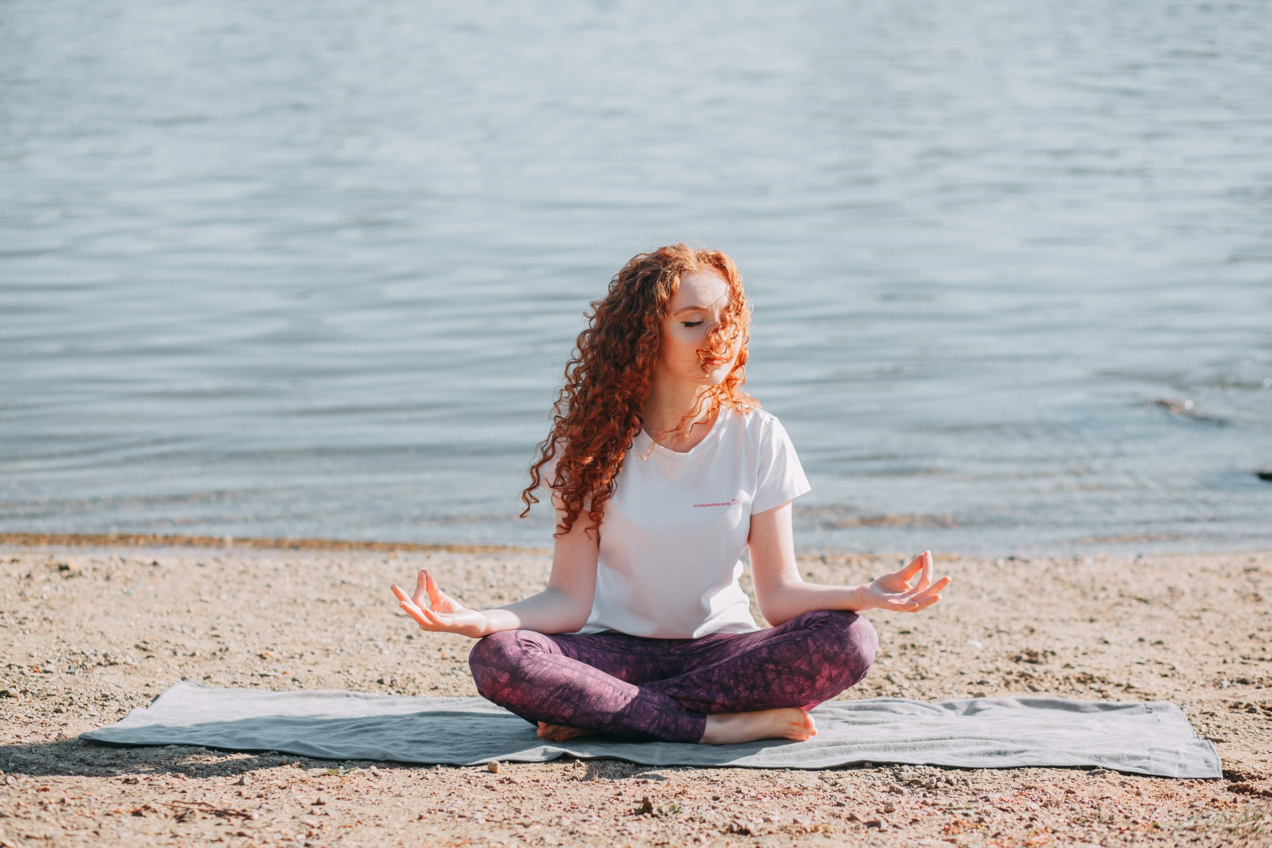 Wellbeing woman doing yoga exercise at the sea shore 3759660 scaled