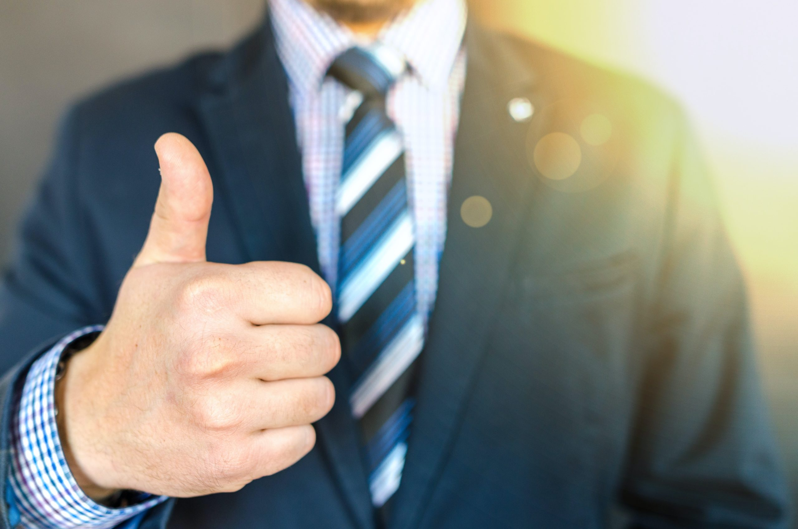 Work Safe close up photo of man wearing black suit jacket doing thumbs 684385 scaled