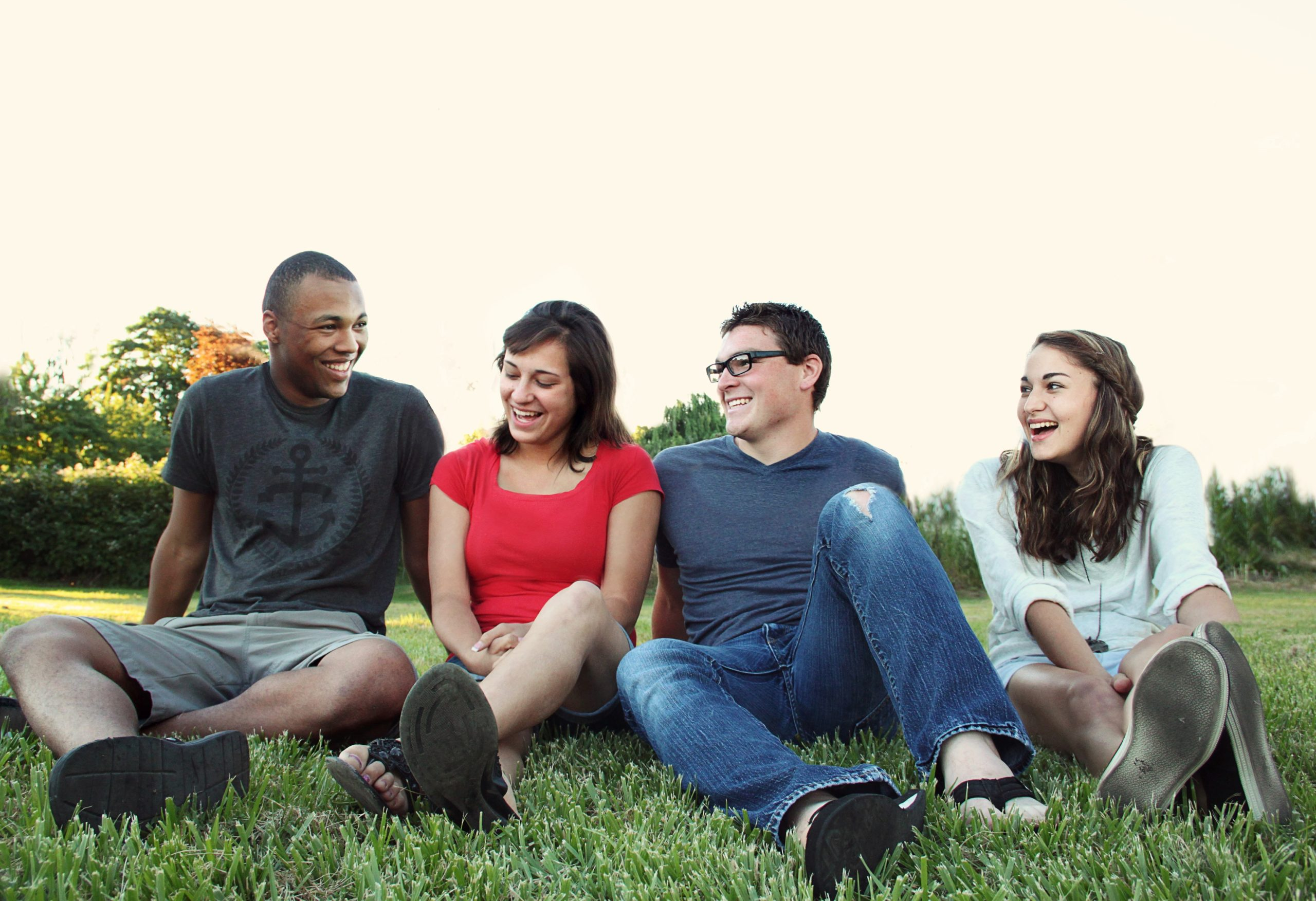 Youth smiling women and men sitting on green grass 1231230 scaled